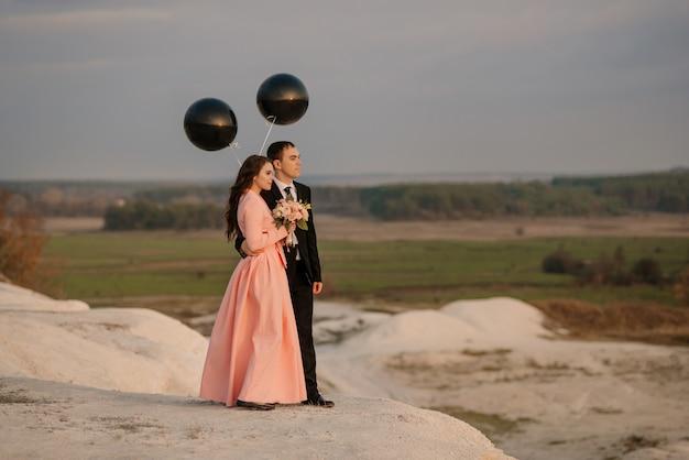 Pasgetrouwden lopen in de natuur met grote helium ballonnen buiten bij zonsondergang. bruiloft concept.