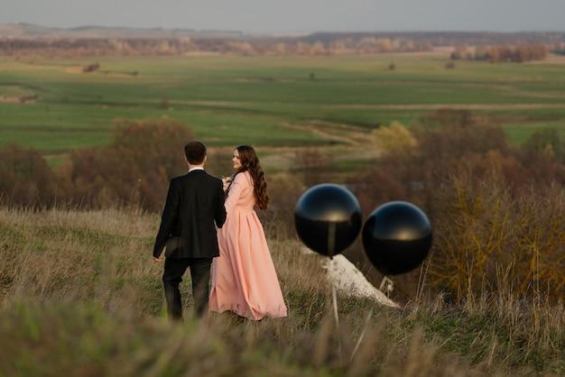 Pasgetrouwden lopen in de natuur met grote heliumballonnen. bruiloft concept.