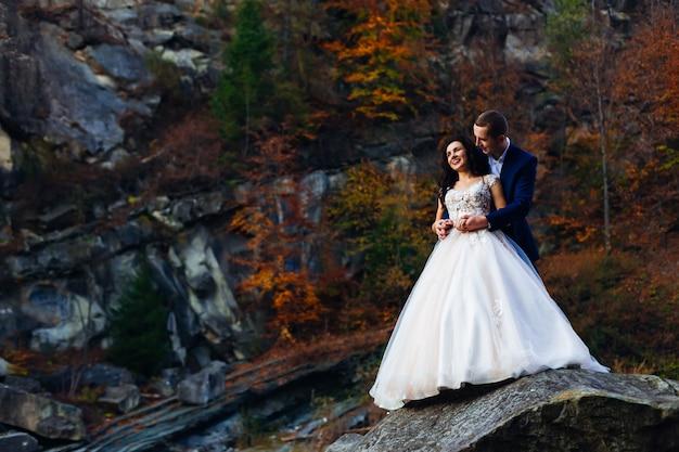 Pasgetrouwden op een grote steen zonder achtergrond van rotsen en herfst