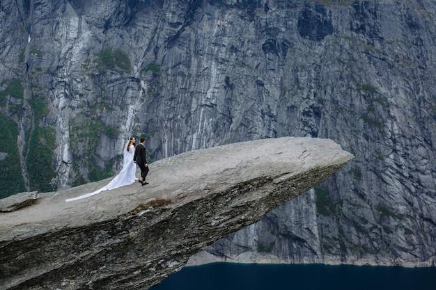 Pasgetrouwden op een rotsfragment in noorwegen genaamd troll's tong