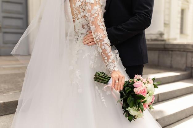 Pasgetrouwden op trouwdag, bruidspaar met bruiloft boeket bloemen
