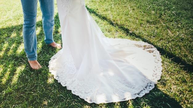 Pasgetrouwden staan op het gras. close-up van een lange witte bruiloft kanten jurk in zonnige hoogtepunten en de bruidegom staat op blote voeten in blauwe broek