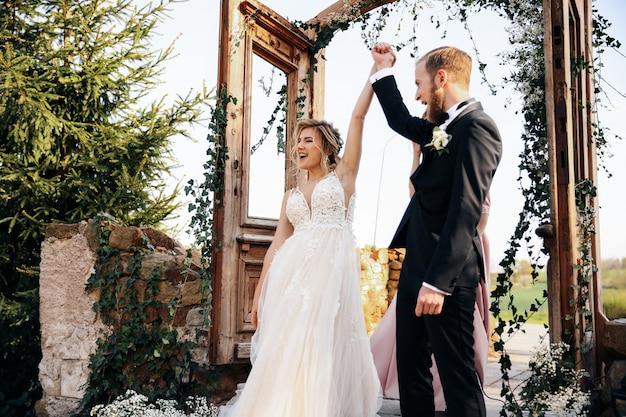 Pasgetrouwden steken hun handen omhoog na afloop van de huwelijksceremonie