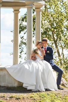 Pasgetrouwden wandelen in de natuur in het park na de huwelijksceremonie een kus en een knuffel van een man en een vrouw