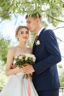 Pasgetrouwden wandelen in de natuur in het park na de huwelijksceremonie. een kus en een knuffel van een man en een vrouw