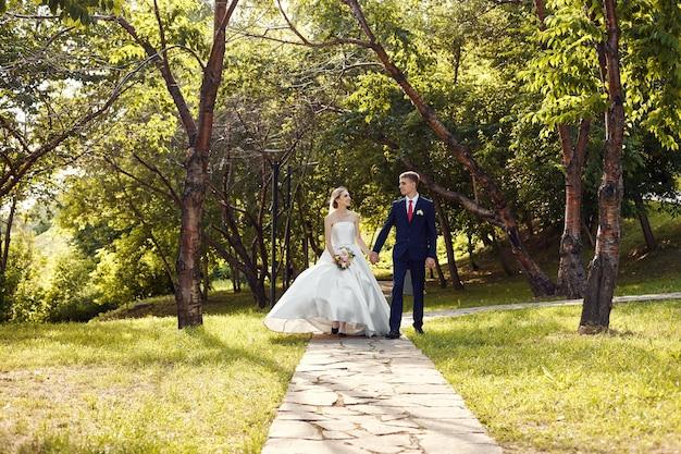 Pasgetrouwden wandelen in de natuur in het park na de huwelijksceremonie
