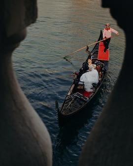 Pasgetrouwden zoenen op de luxe gondel tijdens een rondvaart door de grachten
