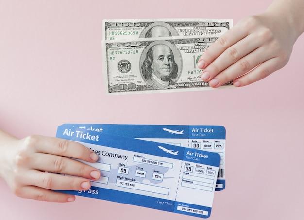 Paspoort, dollars en vliegticket in vrouw hand op een roze