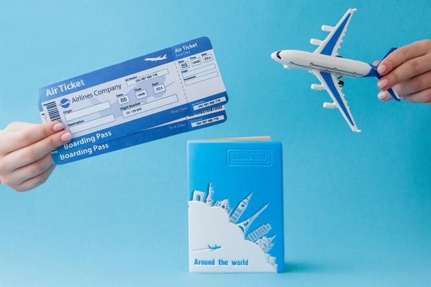 Paspoort, dollars en vliegticket in vrouwenhand op blauw
