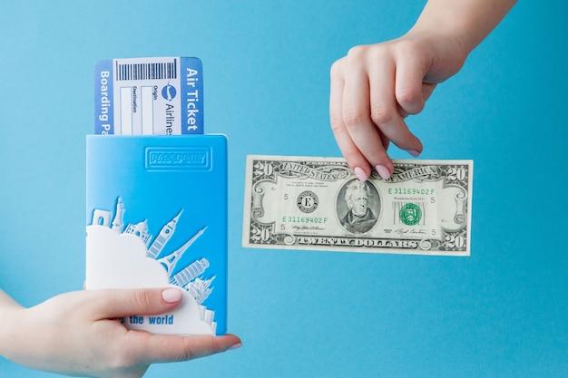Paspoort, dollars en vliegticket in vrouwenhand op een blauw