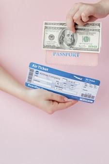 Paspoort, dollars en vliegticket in vrouwenhand op roze