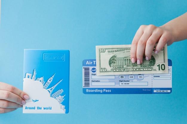 Paspoort, dollars en vliegticket in vrouwenhand. reisconcept, exemplaarruimte