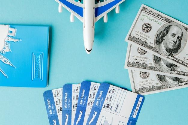 Paspoort, dollars, vliegtuig en vliegticket op een blauwe achtergrond. reisconcept, exemplaarruimte.