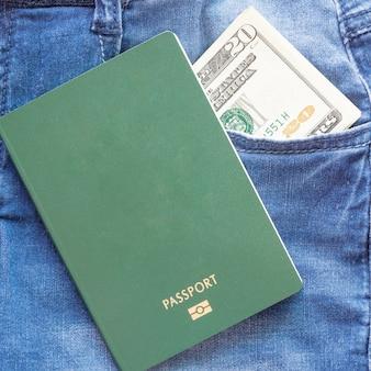 Paspoort en amerikaanse dollars in de achterzak van de jeans