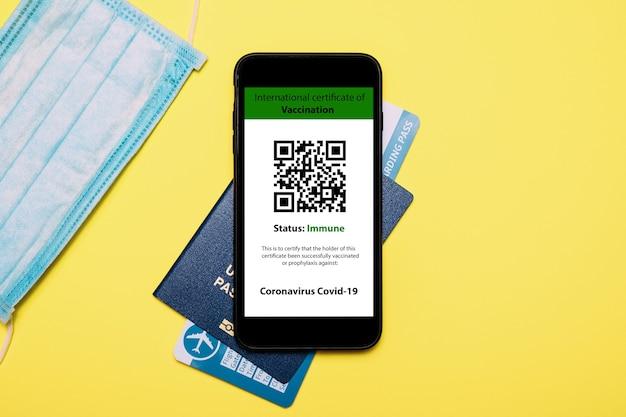 Paspoort en een smartphone met een digitaal certificaat van vaccinatie tegen de ziekte covid-19.