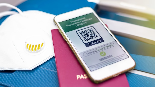 Paspoort en smartphone met internationaal vaccinatiecertificaat covid-19 qr-code op koffer met masker