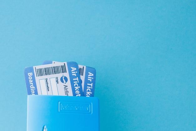 Paspoort en vliegticket in vrouwenhand op een blauw