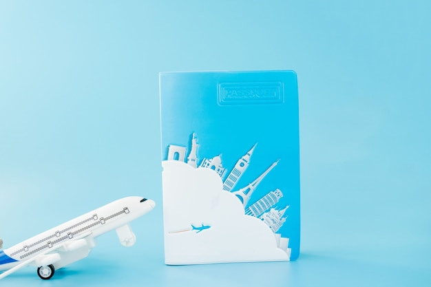 Paspoort en vliegtuig op lichtblauwe achtergrond. zomer of vakantie concept. kopieer ruimte.