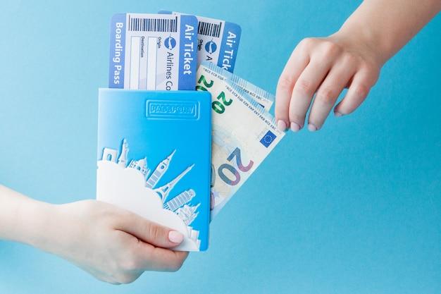 Paspoort, euro en luchtkaartje in vrouwenhand op een blauw. reizen, kopiëren