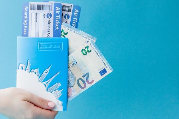 Paspoort, euro en vliegticket in vrouwenhand op een blauwe achtergrond