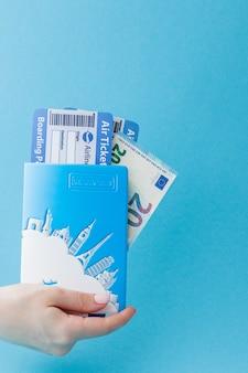 Paspoort, euro's en vliegtickets in de hand van de vrouw