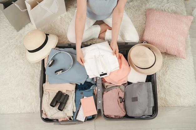 Paspoort in meisjeshand en reisaccessoires kostuums, bagage, camera, kleding in koffer, voorbereid op het reis- en reisconcept