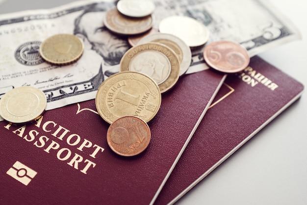 Paspoort met bankbiljetten en munten op een effen achtergrond.