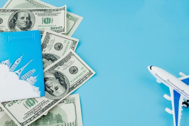 Paspoort met model van passagiersvliegtuig en dollars op blauwe achtergrond. reisconcept, exemplaarruimte.