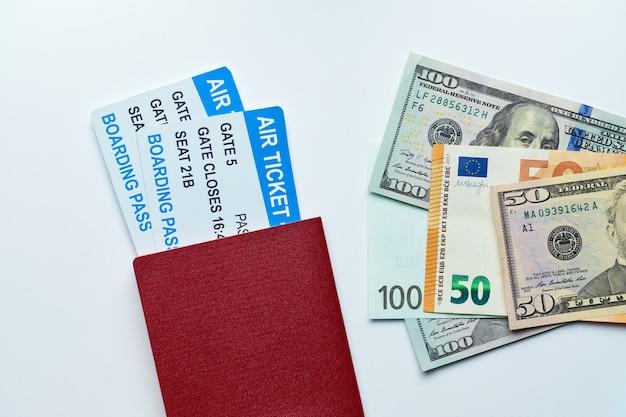 Paspoort met vliegtickets en geld met ons dollars en euro's op wit met bovenaanzicht