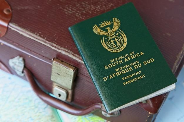 Paspoort op een leren koffer en een geografische kaart