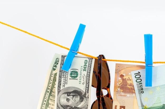 Paspoort, zonnebril, euro, dollarbankbiljetten bevestigd met wasknijpers aan een touw op een witte geïsoleerde achtergrond