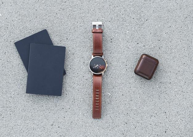 Paspoorten met een horloge en earpods op beton achtergrond