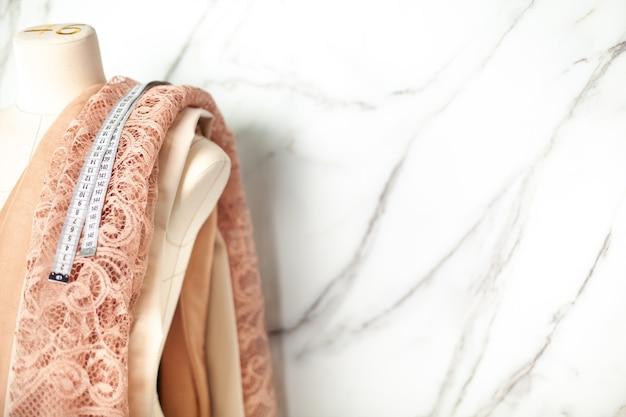 Paspop op maat met koraalkleurige kanten stof en meetlint naast marmeren muur. luxe kanten stoffen met bloemenmotief voor het naaien van trouwjurken, lingerie en bruidsmeisjesjurken. stof van gemengd katoen en zijde.