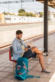 Passagier die bij telefoon aan de gang post glimlacht