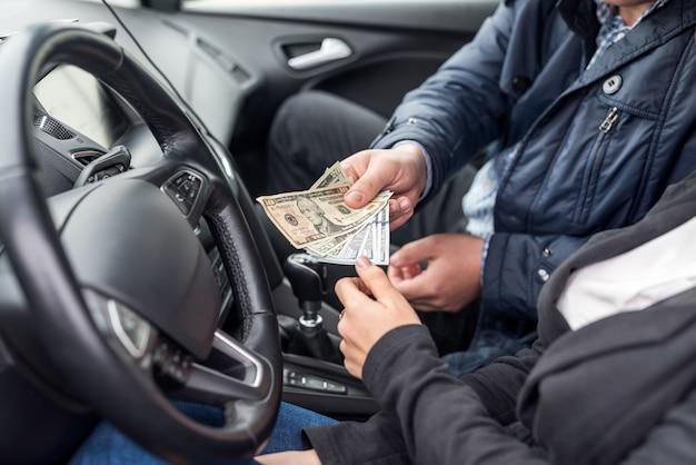Passagier die dollarbankbiljetten geeft aan een chauffeur