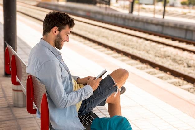 Passagier die op trein op een bank wacht