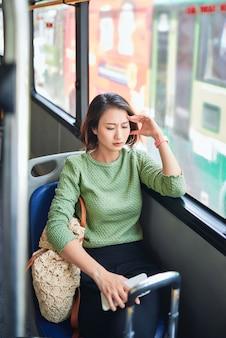 Passagier die reist en zich duizelig voelt met hoofdpijn tijdens een busreis