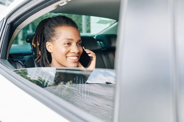 Passagier die telefoon in auto gebruikt