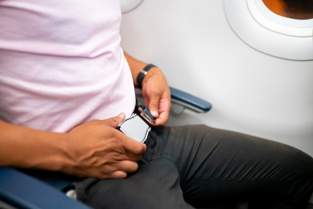 Passagier die veiligheidsgordel vastmaakt terwijl hij in het vliegtuig zit voor een veilige vlucht