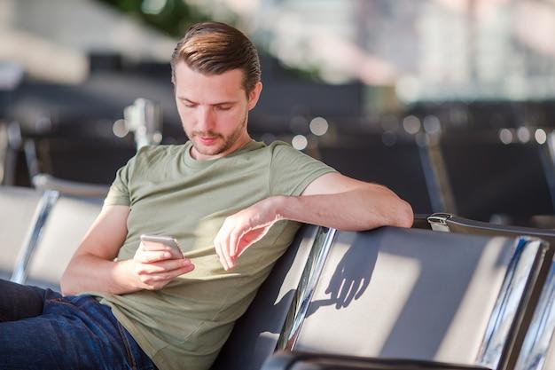 Passagier in een luchthavenlounge die op vluchtvliegtuigen wacht. jonge mens die met cellphone in luchthaven op het landen wacht