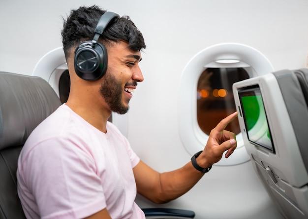 Passagier in vliegtuig entertainment lcd-scherm aan te raken. latijns-amerikaanse man in vliegtuigcabine met behulp van smart-apparaat luisteren naar muziek op de koptelefoon