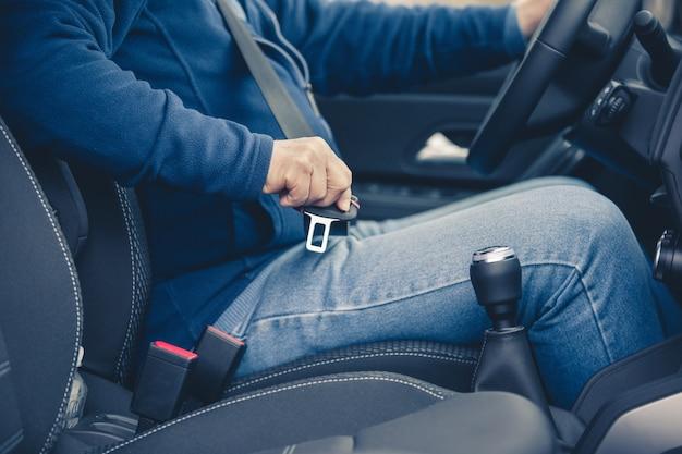 Passagier man bevestiging veiligheidsgordel in de auto, transport en veiligheidsconcept