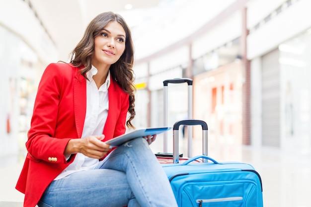 Passagier reiziger vrouw in luchthaven wachten op vliegreizen met behulp van tablet smartphone.