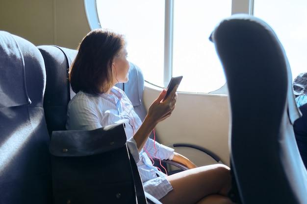 Passagier van de volwassen vrouw van de zeeveerboot die in de cabine van de boot reist. vrouw zittend op fauteuil rusten, met behulp van smartphone. zeetransport, reizen, toerisme