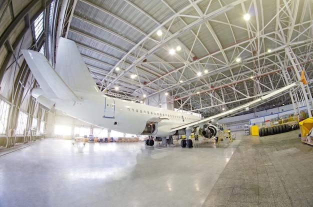 Passagiersvliegtuig betreffende onderhoud van motor, romp en hulpaggregaat. controleer reparatie in de hangar van de luchthaven. vliegtuigzicht achterzijde, met open bagageruimte.