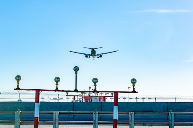 Passagiersvliegtuig dat in de blauwe hemel in zonlichtstralen vliegt