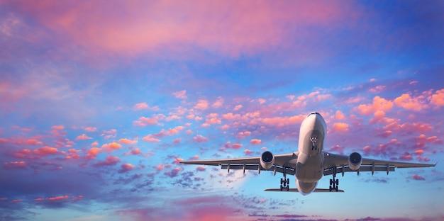 Passagiersvliegtuig dat met roze wolken vliegt