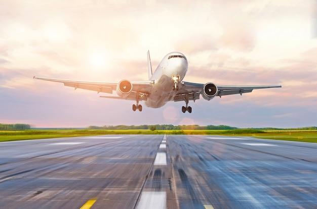 Passagiersvliegtuig die bij zonsondergang op een landingsbaan landen.