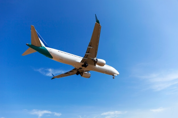 Passagiersvliegtuig die duidelijke blauwe hemel en wolkenachtergrond landen