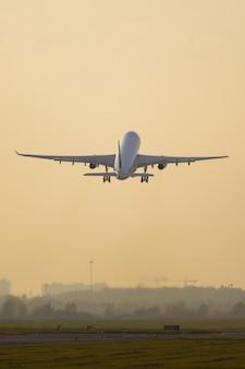 Passagiersvliegtuig met brede romp die op zonsondergang van start gaan